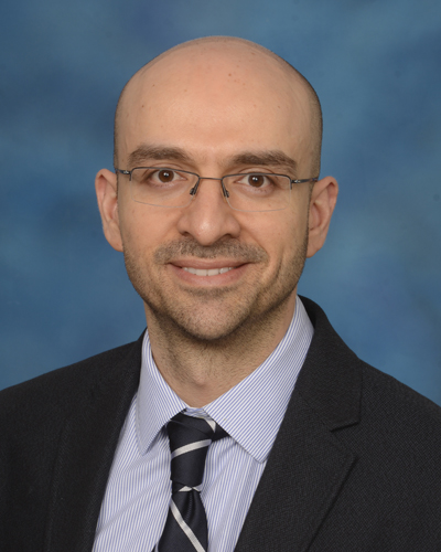 Photo of Alex Poulopoulos, PhD in a black suit, light blue shirt, and black tie, in front of a blue background